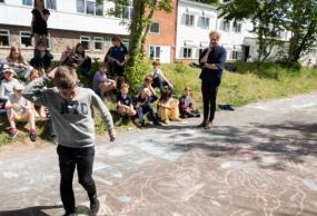 Klassen tegner katte med kridt i skolegården